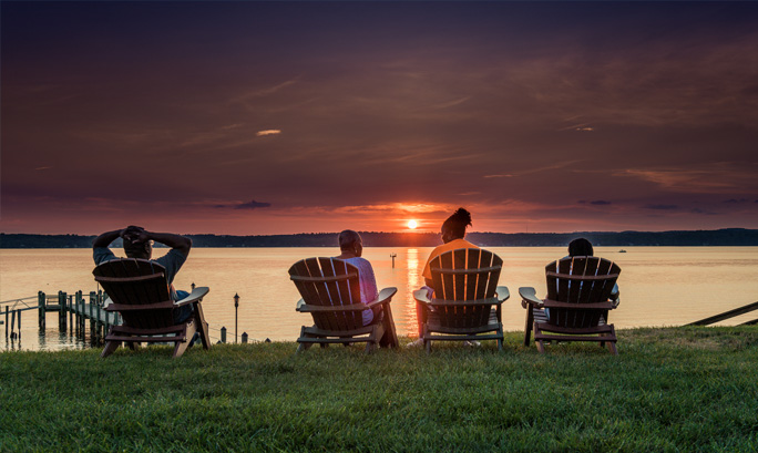 A couple sitting in Adirondack chairs watch a beautiful sunset over the lake.